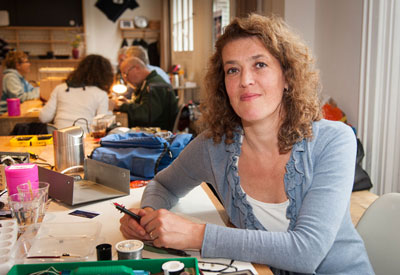 Smiling woman sitting at a work table covered with various tools. In the background, people work together on repairs.