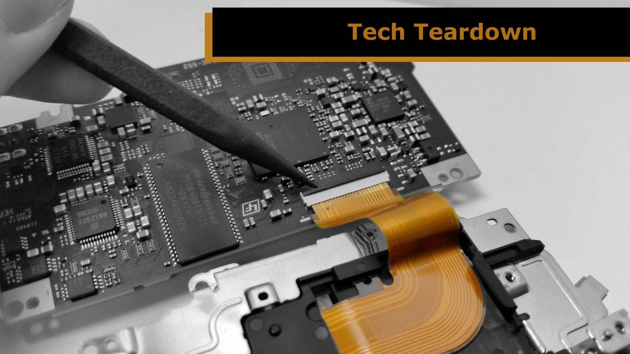 """Close up of someone using a spudger to work on a circuit board. The words """"Tech Teardown"""" appear in the upper right corner of the image."""